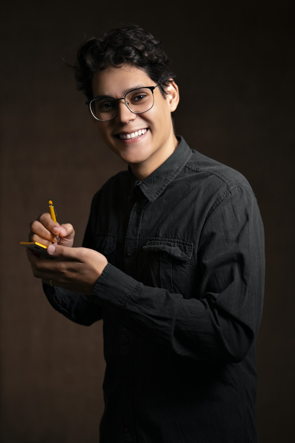 smiling man wearing black denim jacket holding pencil and sticky note while standing