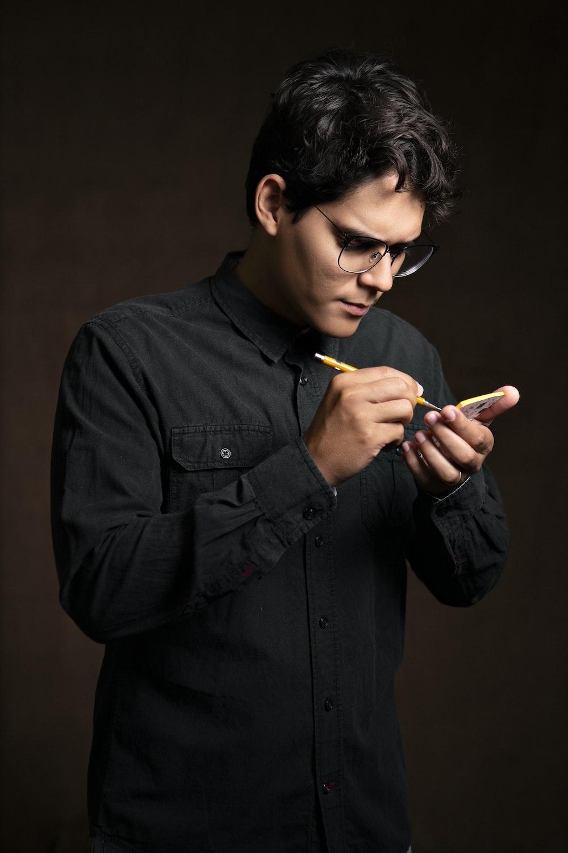 man writing on smartphone using stylus pen