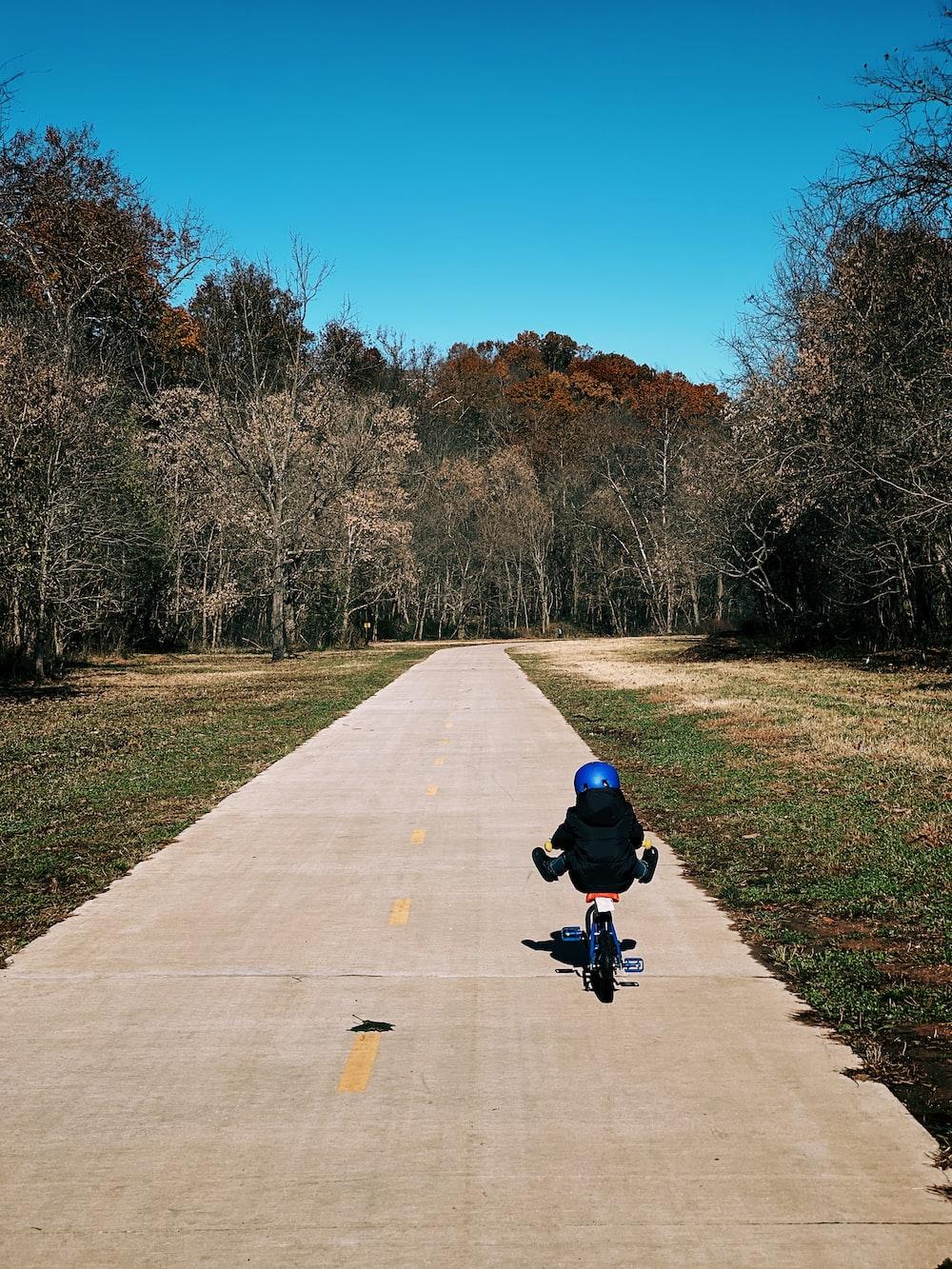 child biking on road near green field during daytime