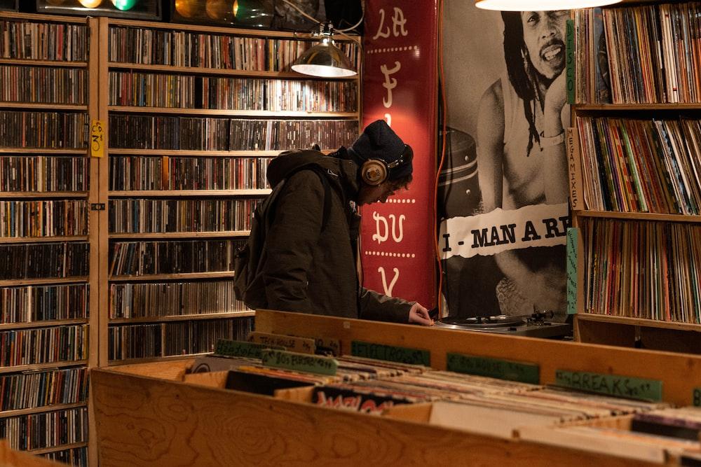 man in hoodie and headphones standing inside record store