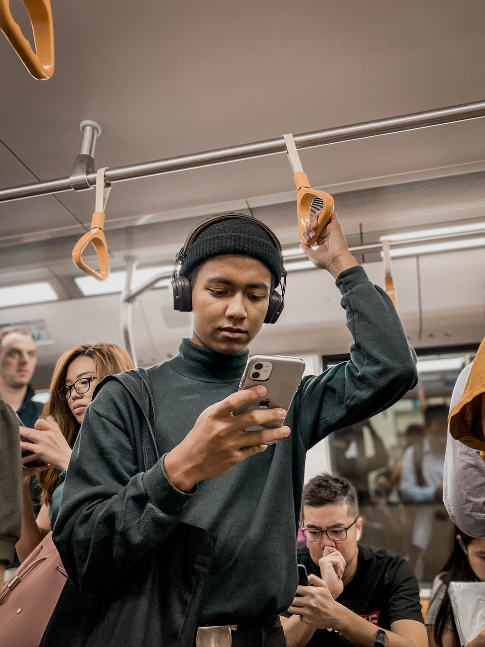 man in train holding smartphone
