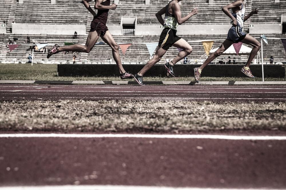 three running people on race tracks