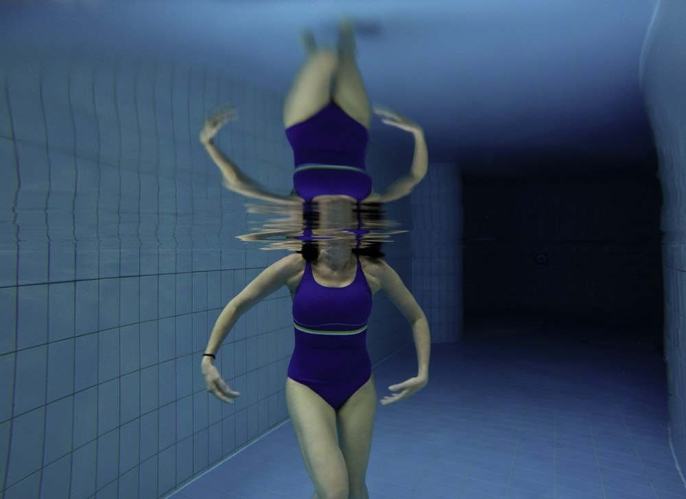 under water photography of woman wearing blue bodysuit