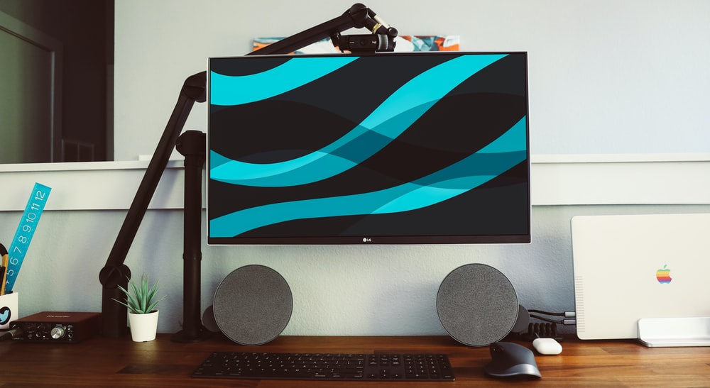 flat screen monitor beside wall and pair of gray speakers