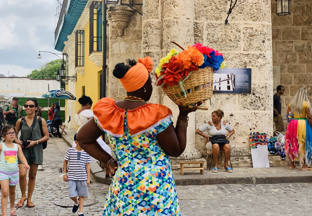 standing woman holding basket of flowers