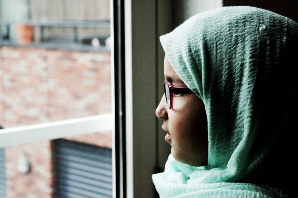woman looking outside of the window during daytime
