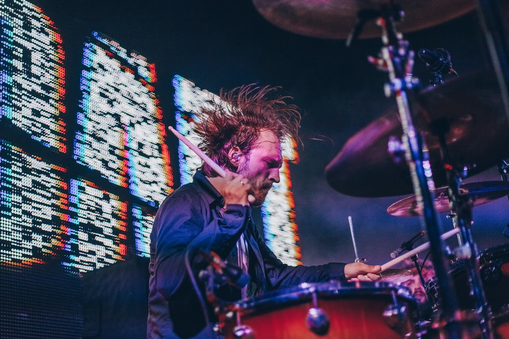 selective focus photography of man playing drums