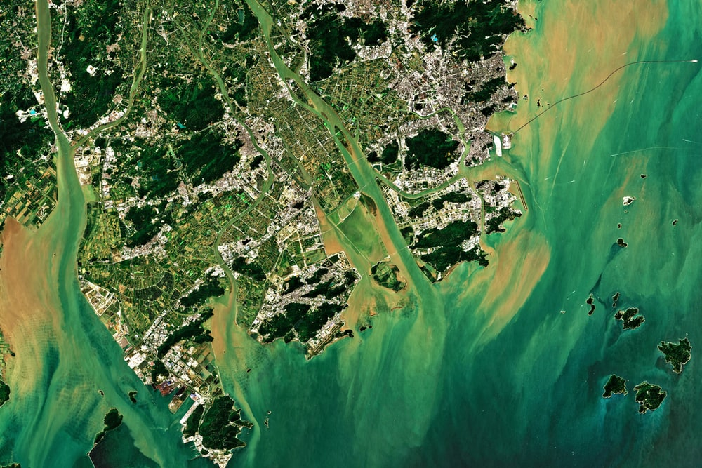 aerial photography of green field surrounded with body of water