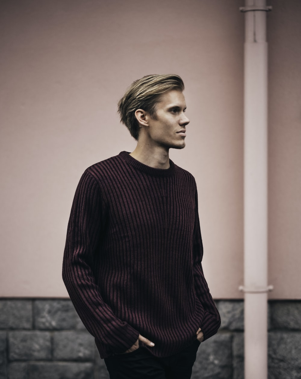 man in brown sweater standing beside wall
