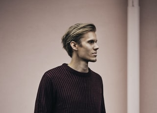 man in brown sweater standing beside wall