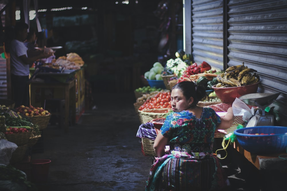 woman in floral top by displayed fruits and vegetables