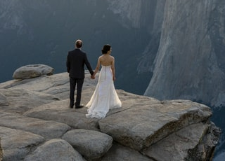 bride and groom standing on rocky hill viewing Yosemite National Park during daytime