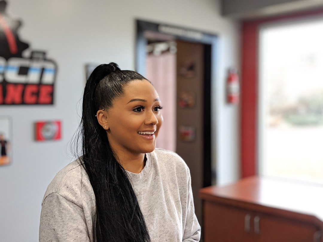 Woman of Color in grey sweats smiling.