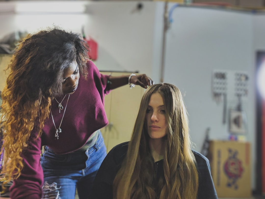 A stylist in a burgundy crop top works with her model before a shoot. Shot inside a repair shop located in Sterling Virginia.