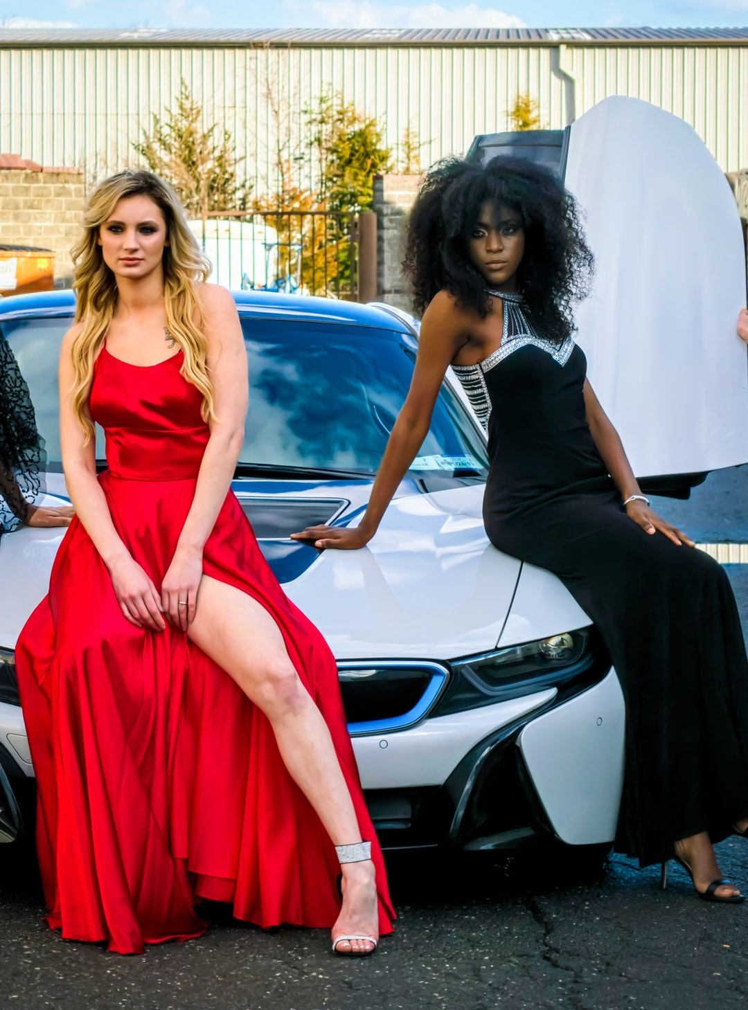 Two women in gowns sitting on a BMW. This was taken outside of a repair see shop in Sterling Virginia. This photoshoot was funded and managed by the models themselves.