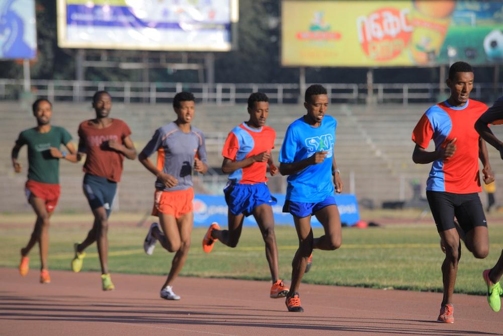 men running near bleachers