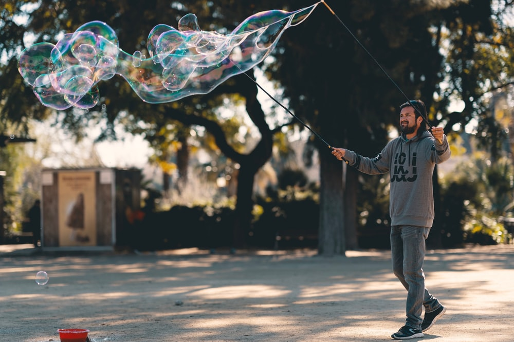 man wearing grey and black sweater doing bubbles during daytime