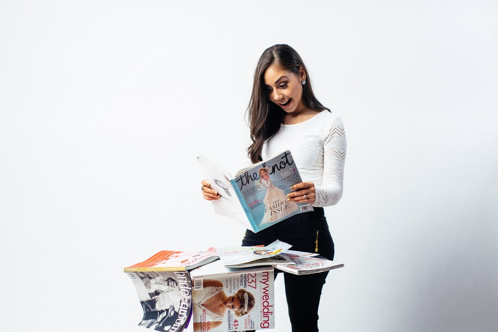 woman standing in front of magazine holding The Knot magazine