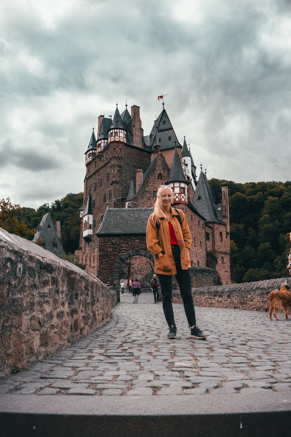 woman wearing jacket standing near castle during daytime