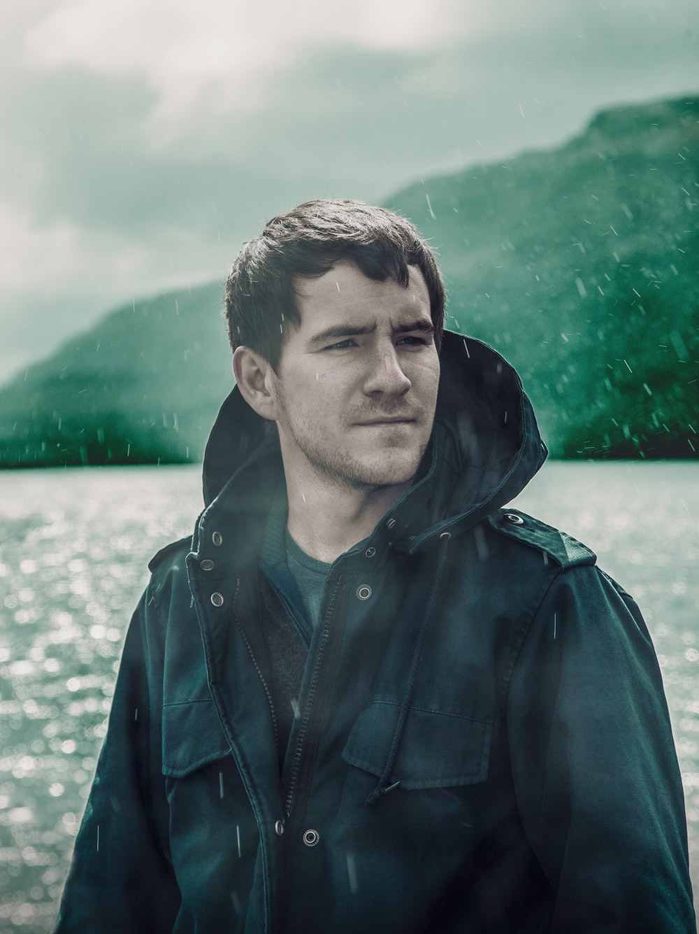 man wearing black zip-up jacket standing near body of water in rainy day