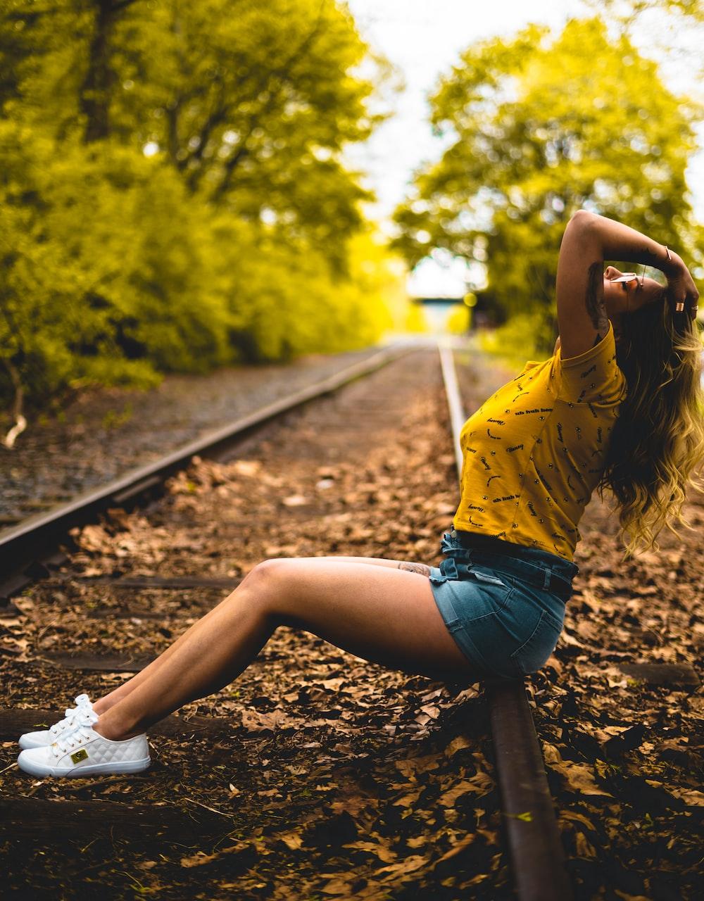 woman sitting on railroad in macro photography