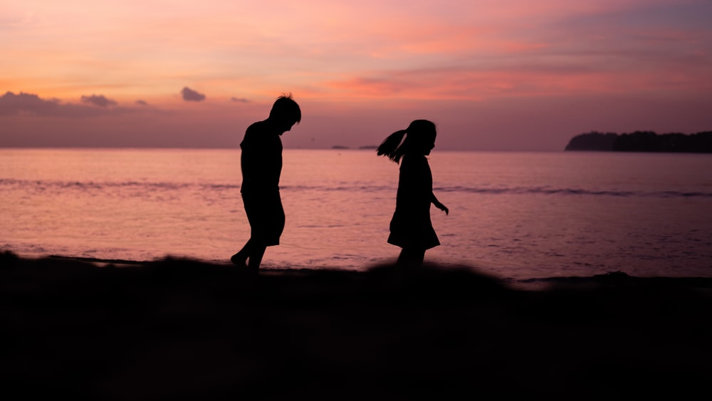 silhouette photography of boy and girl walking beside shoreline