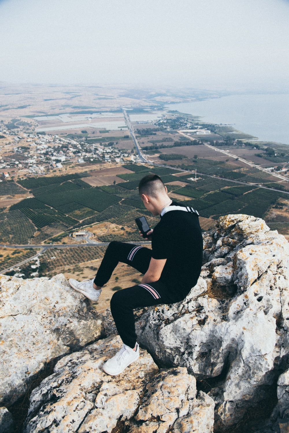 man wearing black t-shirt using phone while sitting on rocky hill viewing houses on green field during daytime