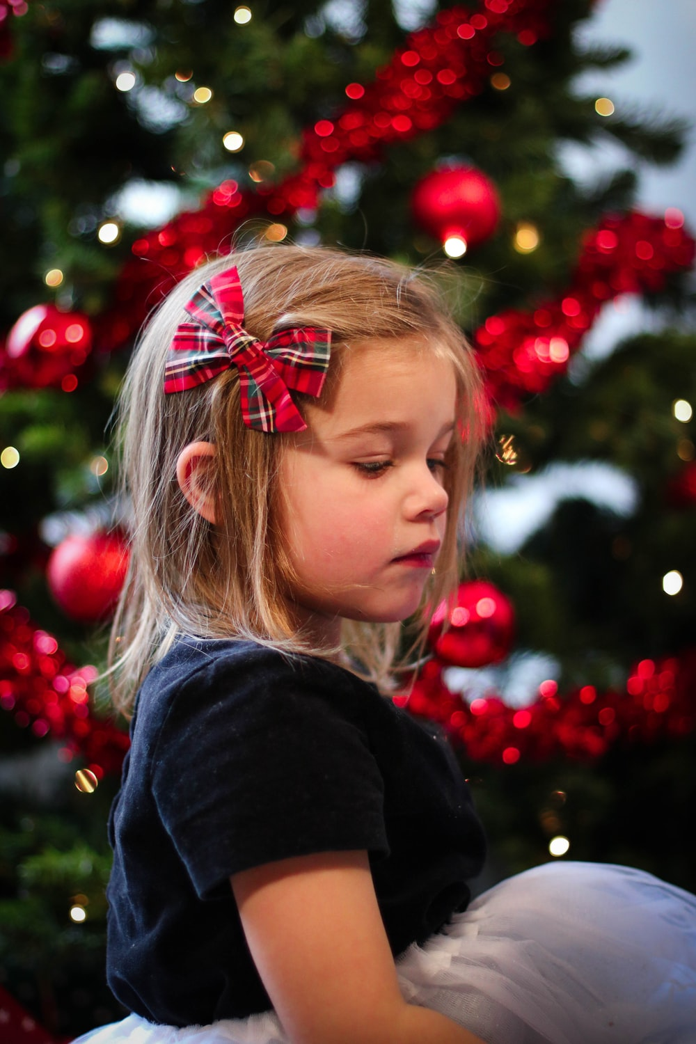 girl in black sweater with red and green ribbon on her head