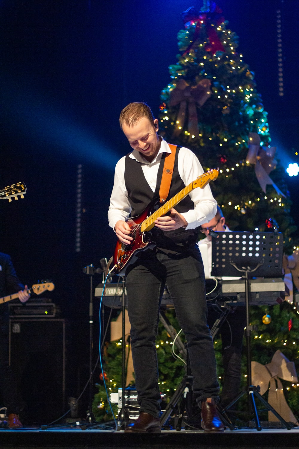 man playing red and brown guitar beside Christmas tree