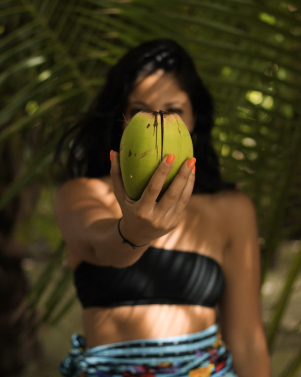 woman wearing black bandeau standing while holding green coconut
