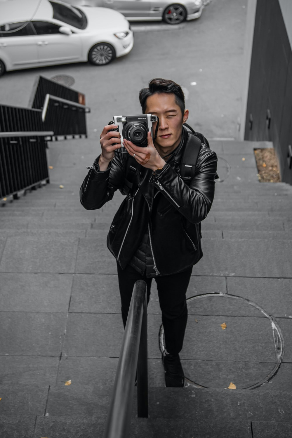 shallow focus photo of man in black leather jacket using camera