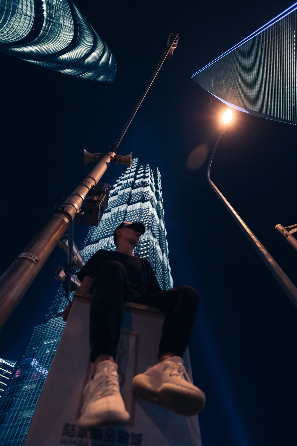 man sitting at the city during night