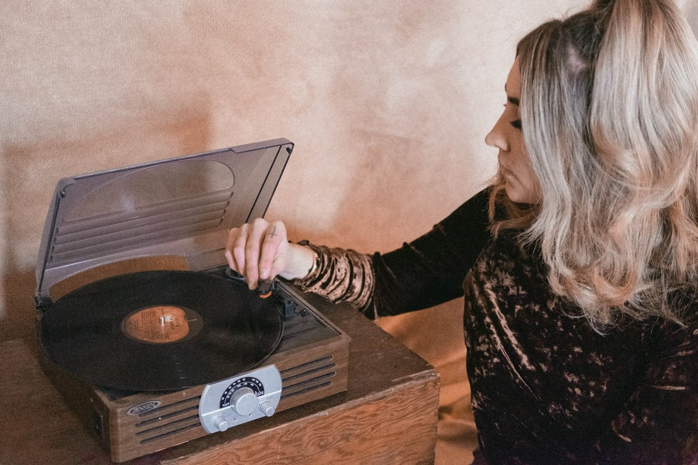 shallow focus photo of woman using brown vinyl player