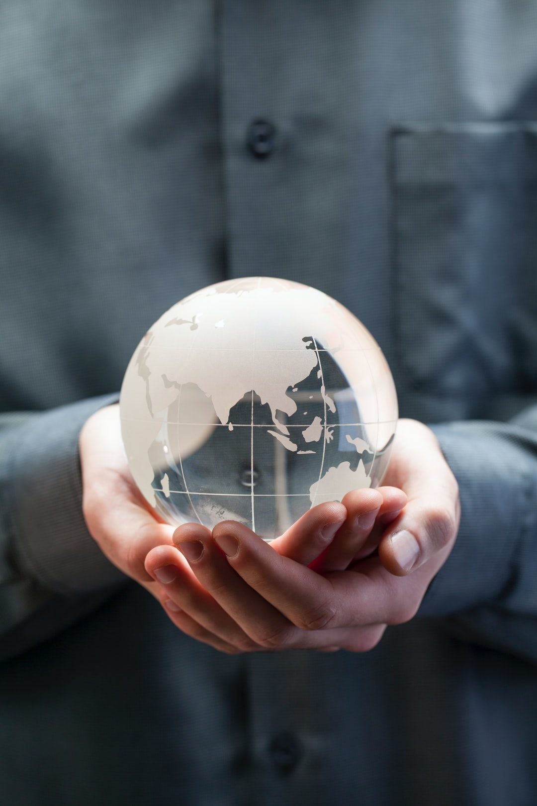 Man holding glass globe in hands. Concept for CHINA global warming, climate change, environmental protection.