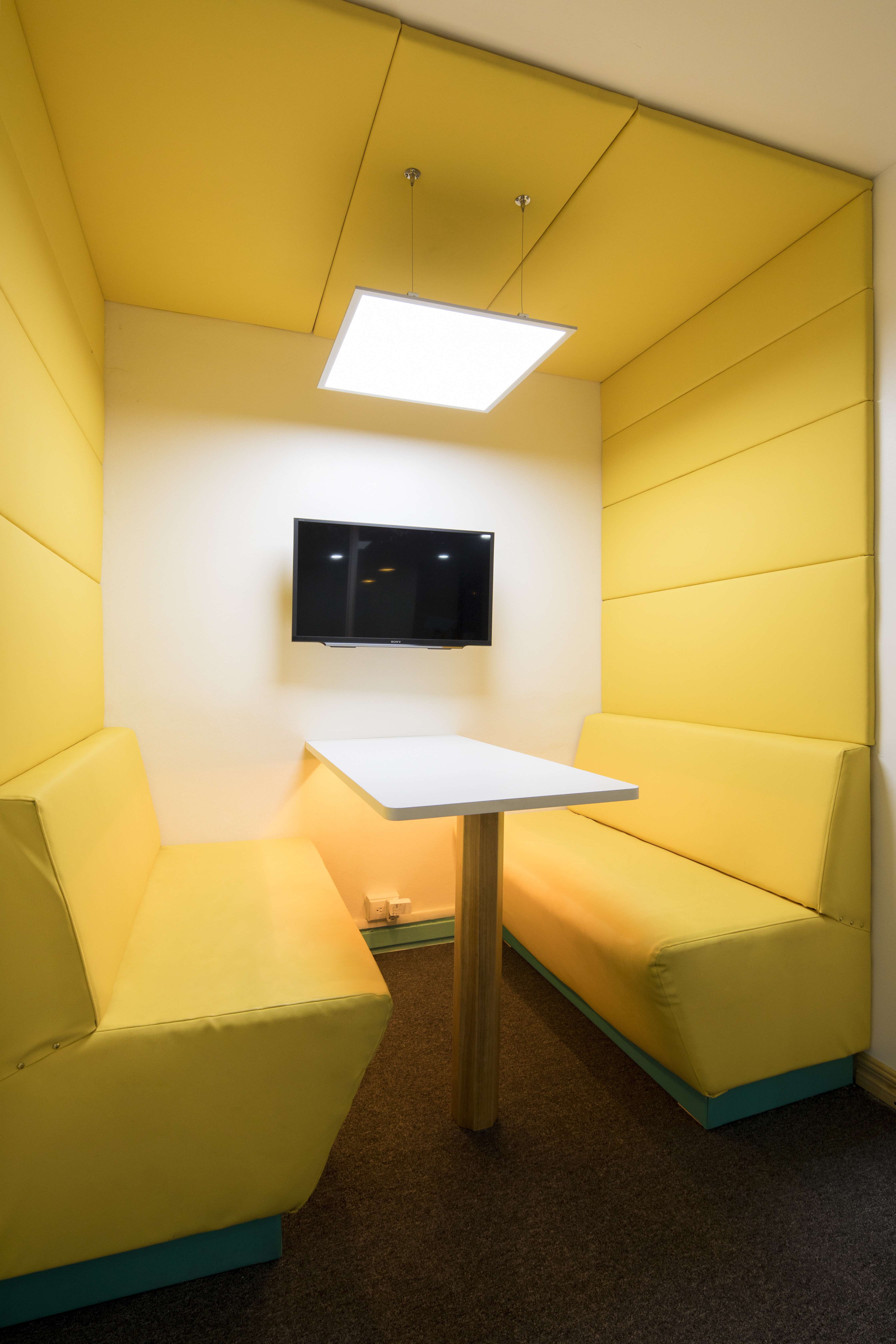 rectangular white wooden table near yellow padded couch