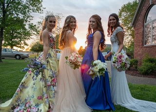 women in dress holding flower bouquets