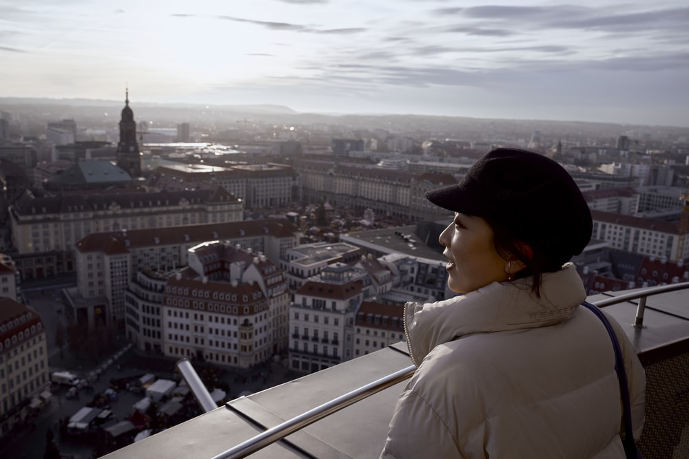 woman standing on rooftop looking at buildings
