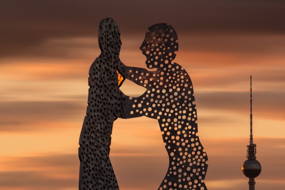 silhouette of two standing men statue during golden hour