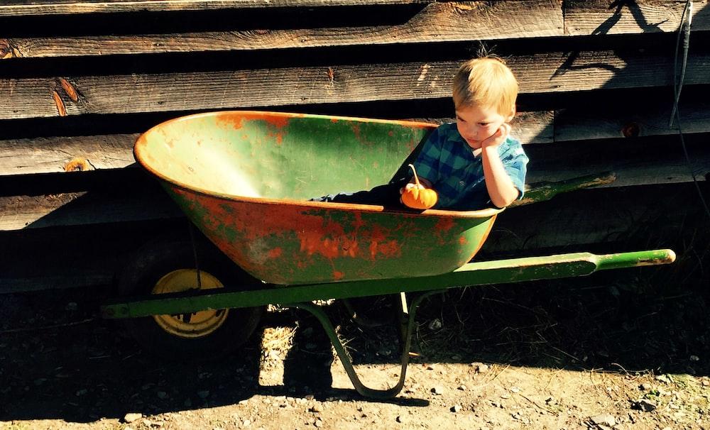 boy riding green wheelbarrow
