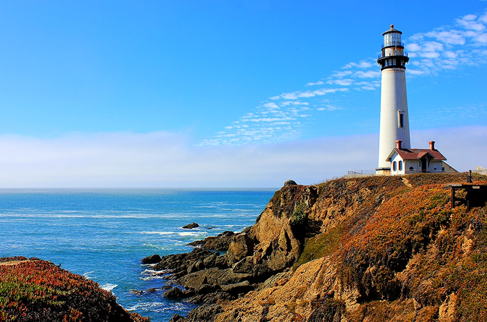 white lighthouse on cliff