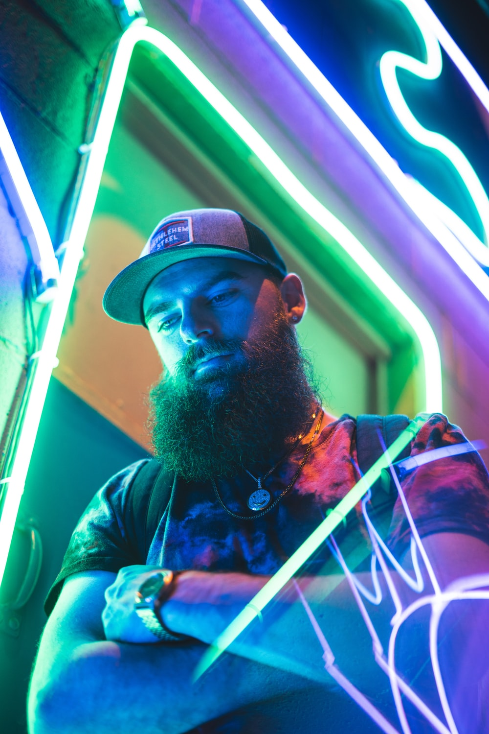 low-angle photography of a bearded man beside a green neon light signage