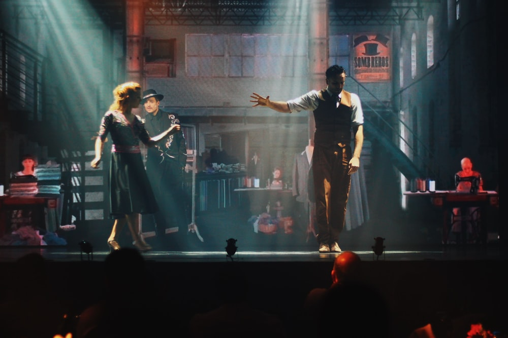 man and woman singing on stage