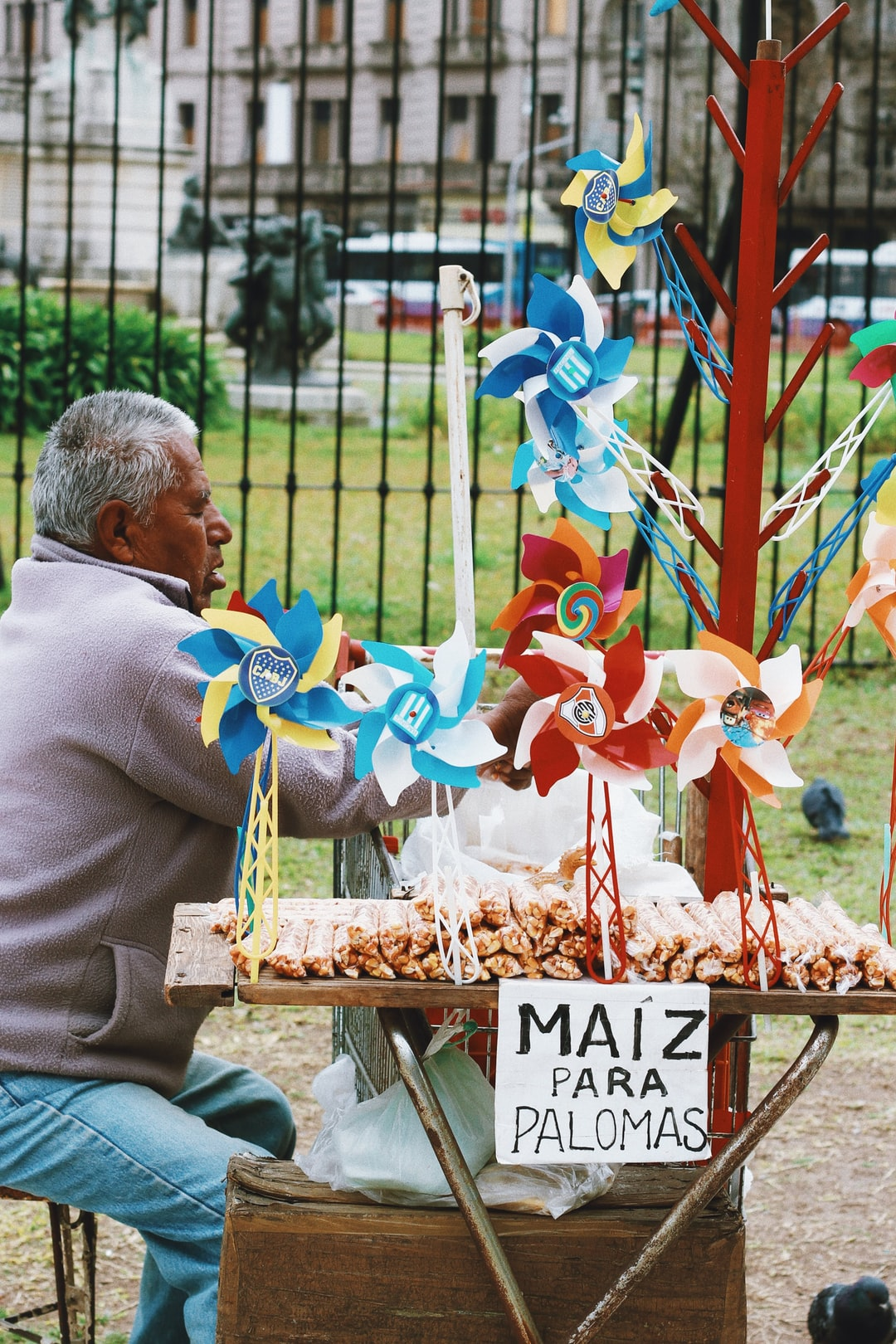 Homem vendendo comida para pombas