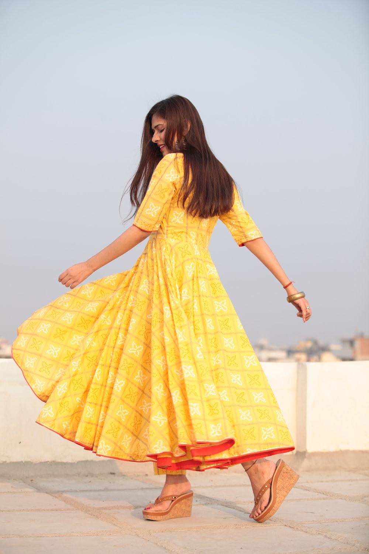 woman swishing her yellow long-sleeved maxi dress