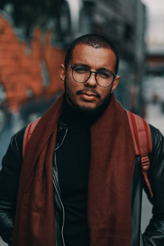 man wearing brown scarf and black jacket