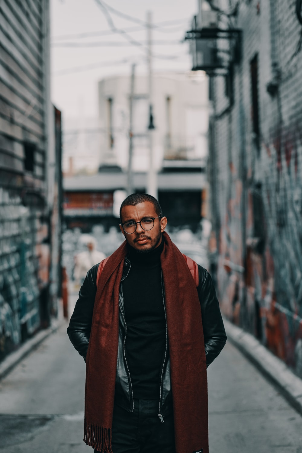 selective focus photo of man wearing brown scarf and black jacket