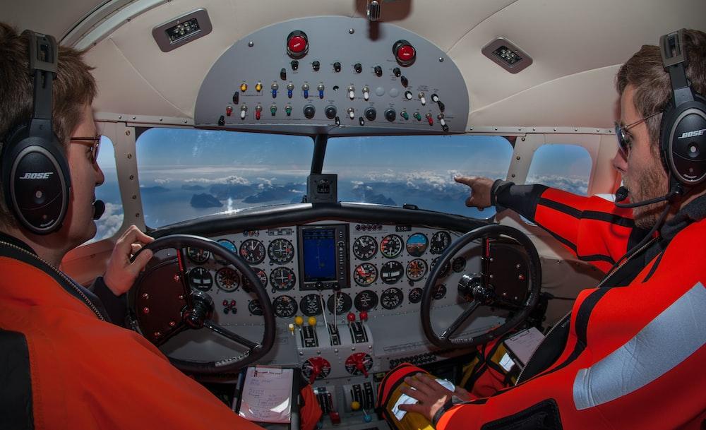 two male pilots inside a cockpit