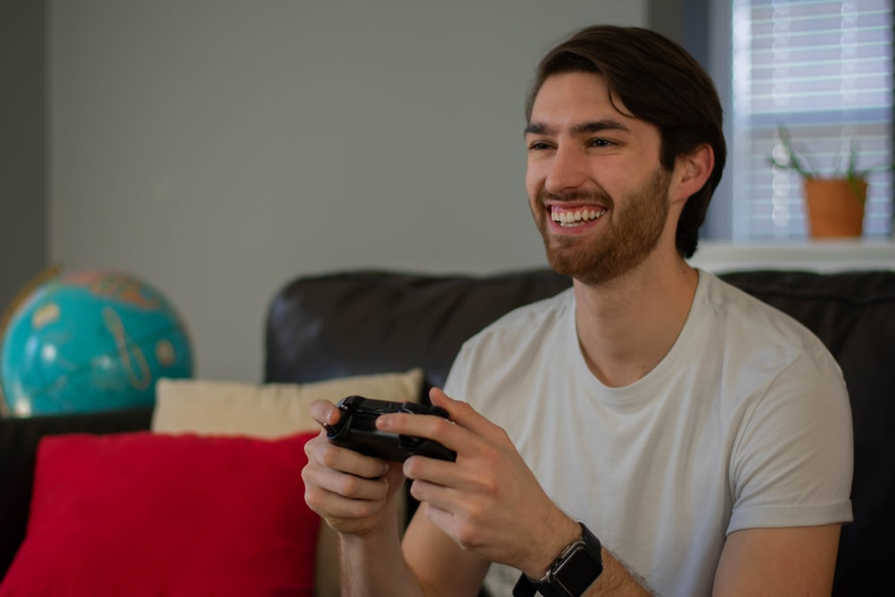 smiling man holding game controller