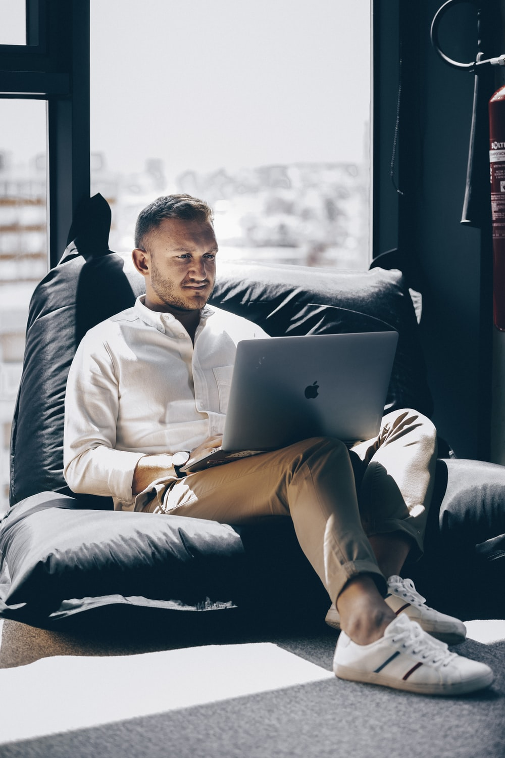man sitting on bed chair while using silver MacBook near window during daytime