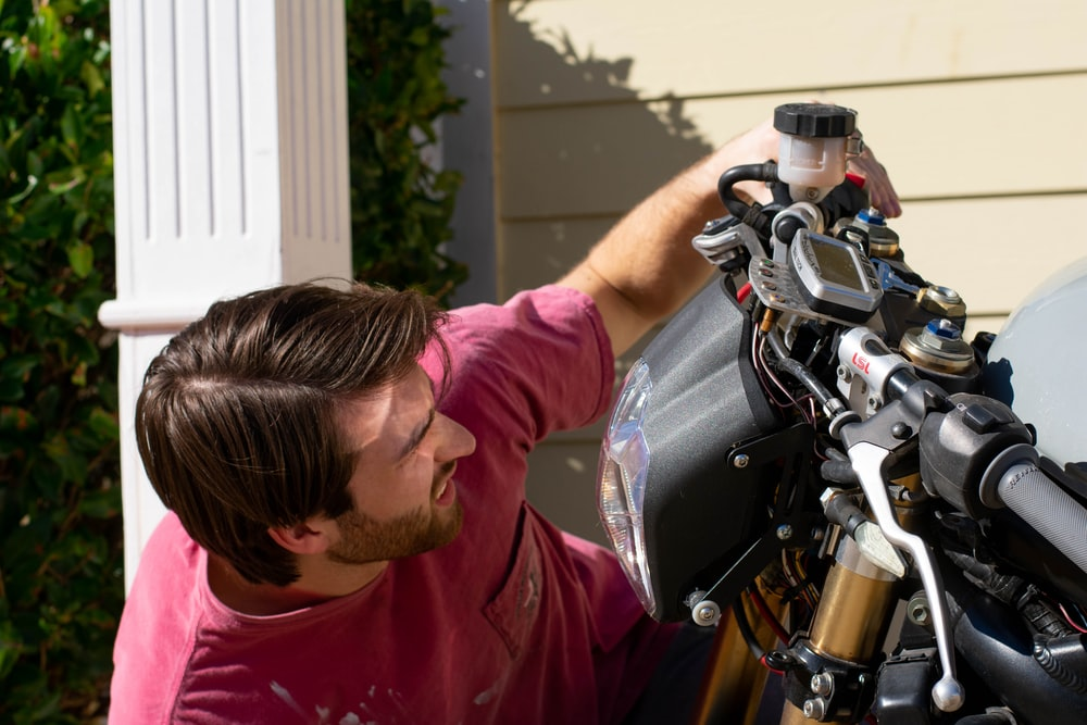 shallow focus photo of man looking at motorcycle headlight